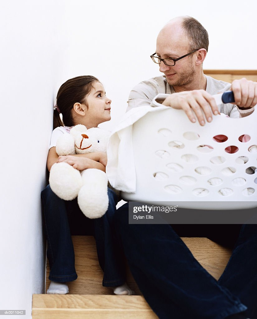 Man Sits on the Stairs With a Laundry Basket Next to His Young Daughter Holding a Teddy Bear : Stock Photo