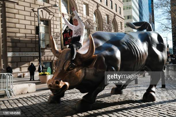 Man sits on the Wall street bull near the New York Stock Exchange on November 24, 2020 in New York City. As investor's fear of an election crisis...