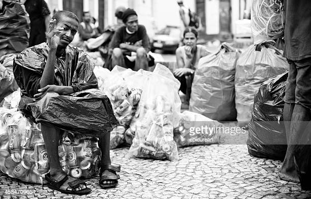 homem senta-se no topo de um saco cheio de latas de lixo - com fome - fotografias e filmes do acervo