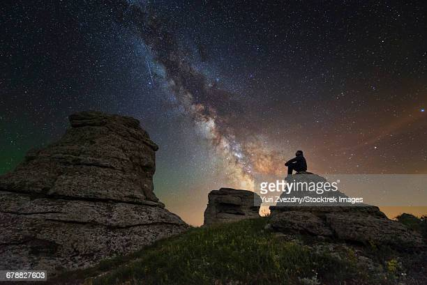Man sits on top of Demerdzhi mountain under the Milky Way at night in Alushta, Crimea.
