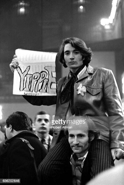 A man sits on top of his friends shoulders while holding a sign that says Yippie at the Grand Central Station in April 1968 in New York New York