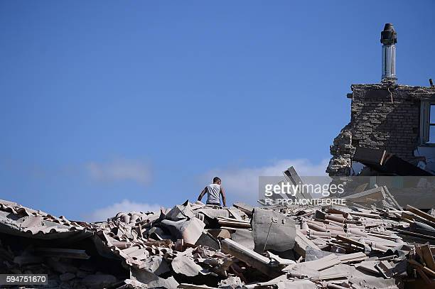 TOPSHOT A man sits on top of rubble in Amatrice on August 24 2016 after a powerful earthquake rocked central Italy The earthquake left 38 people dead...