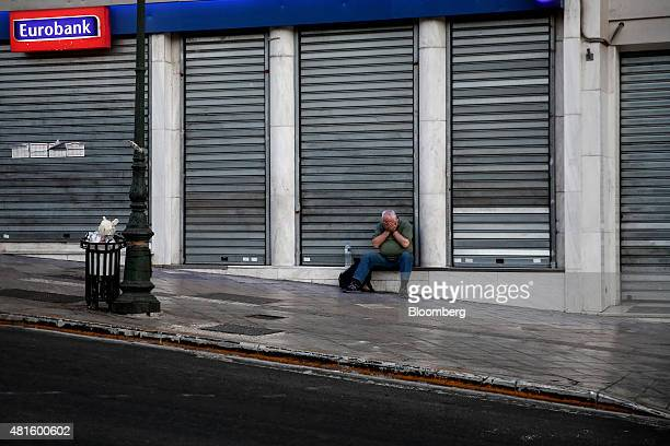 A man sits outside a shuttered Eurobank Ergasias SA bank branch in Athens Greece on Wednesday July 22 2015 Finance Minister Euclid Tsakalotos tried...
