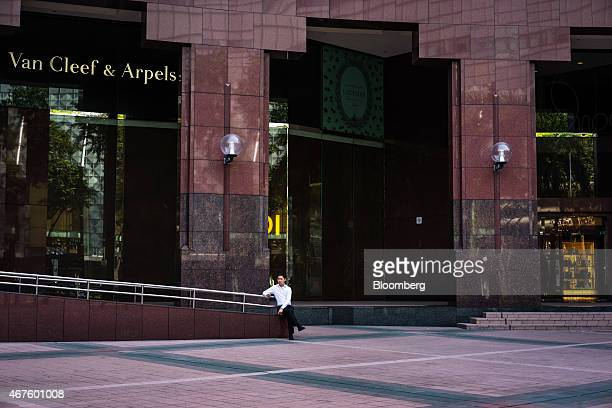 Man sits outside a Van Cleef & Arpels store, a unit of Cie. Financiere Richemont SA, on Orchard Road in Singapore on Wednesday, March 25, 2015. Lee...