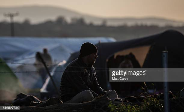 A man sits outside his tent at the Idomeni refugee camp on the Greek Macedonia border on March 19 2016 in Idomeni Greece Thousands of migrants remain...