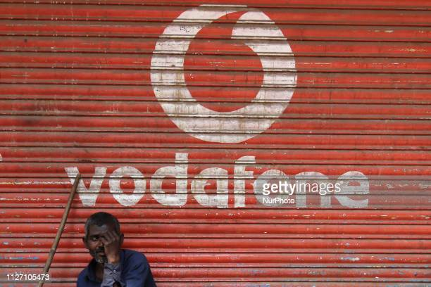 Man sits outside the downed shutters of a shop painted with a logo of Vodafone on its shutter in Mumbai, India on 24 February 2019. India's largest...