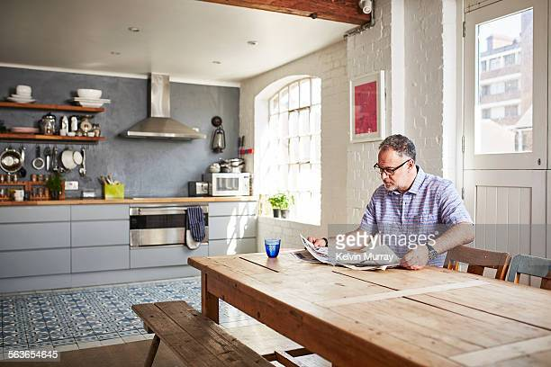 A man sits reading a newspaper at a dining table