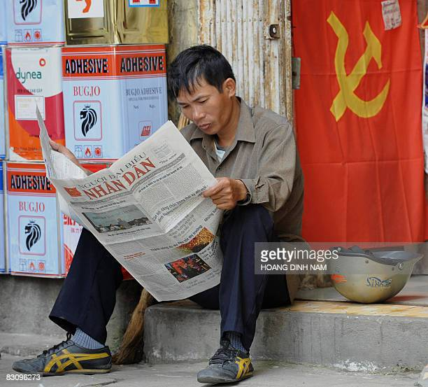 A man sits reading a newspaper in downtown Hanoi on October 3 2008 Vietnam's rulling communist party's central committee is discussing economy issues...