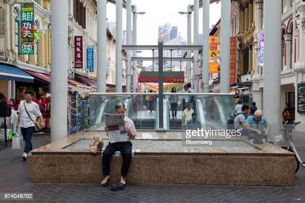 A man sits reading a newspaper nest to an escalator in the Chinatown area of Singapore on Wednesday June 13 2018 Tourism as well as the consumer...