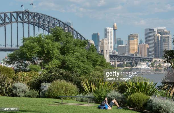 A man sits reading his phone in a park in Lavender Bay on April 9 2018 in Sydney Australia Sydney has been experiencing unseasonably high...