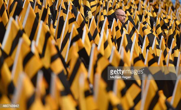 A man sits surrounded by Wasps flags placed on seats before the Aviva Premiership match between Wasps and London Irish at the Ricoh Arena on December...