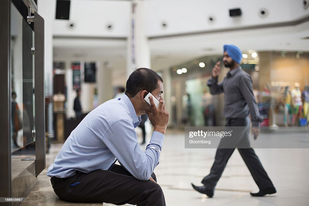 A man sits talking on his mobile phone at the AlphaOne shopping mall in Amritsar India on Thursday May 9 2013 India's consumer price index for April..