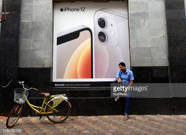 Man sits under a billboard of Apple iPhone 12 in Kolkata, India, 17 August, 2021.