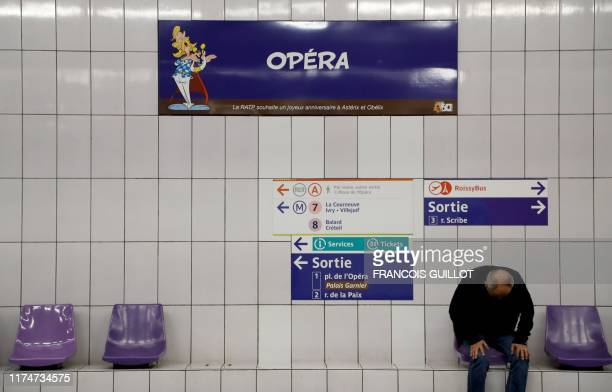 A man sits under a metro station sign especially designed to commemorate the 60th anniversary of France's famous comic characters Asterix and Obelix...
