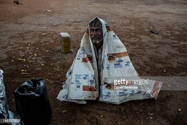 A man sits under a plastic sheet as he takes shelters from a rain storm at the India Gate monument on June 5 2012 in New Delhi India Rains gave some...