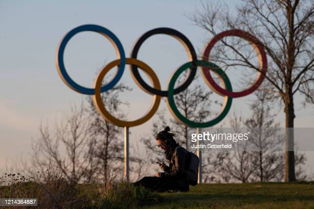 A man sits under he Olympic rings in the Olympic Park in Stratford as Tokyo Olympics organisers are considering options to delay the Olympics with...