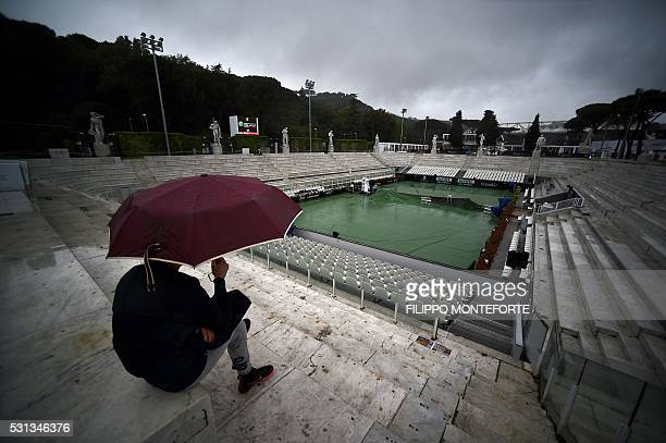 TOPSHOT A man sits under the rain with his umbrella at the Pietrangeli court as Tennis Open tournament at the Foro Italico in Rome is suspended due...