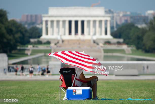A man sits under the shade of an umbrella near the National World War II Memorial and Lincoln Memorial on the National Mall in Washington DC August...
