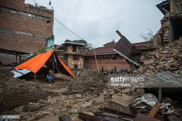 Man sits underneath a tent set up in front of his collapsed home on April 30, 2015 in Bungamati, Nepal. A major 7.8 earthquake hit Kathmandu mid-day...