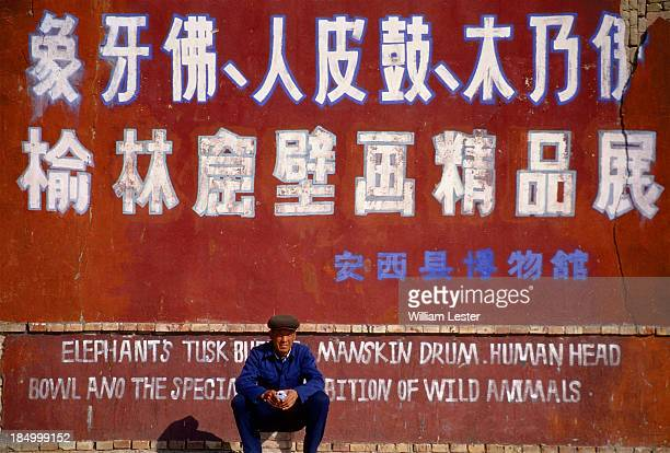 """Man sits, waiting, in front of a sign for a roadside attraction in Gansu Provence, China, 1997. Seen along the silk road, the Sign reads: """"Elephant's..."""
