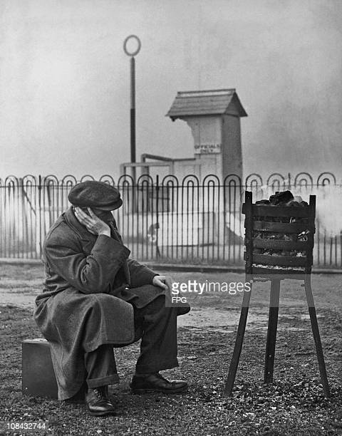 A man sits warming himself by a brazier at Hawthorn Hill racecourse in England after the meeting was abandoned in October 1938