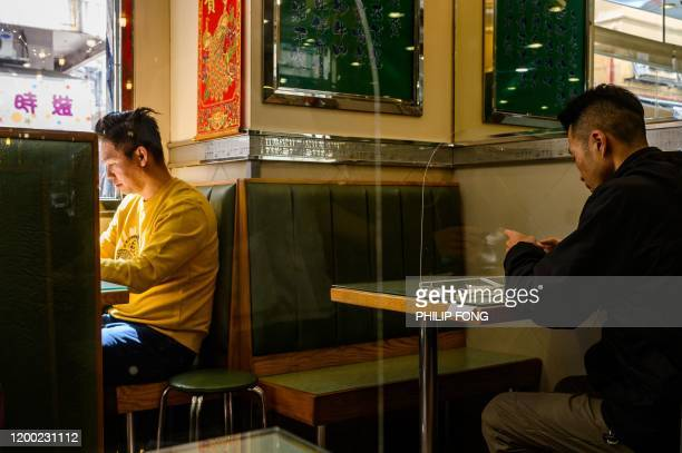 Man sits with a barrier on, as a preventative measure against the COVID-19 coronavirus, in a restaurant in Kowloon district of Hong Kong on February...