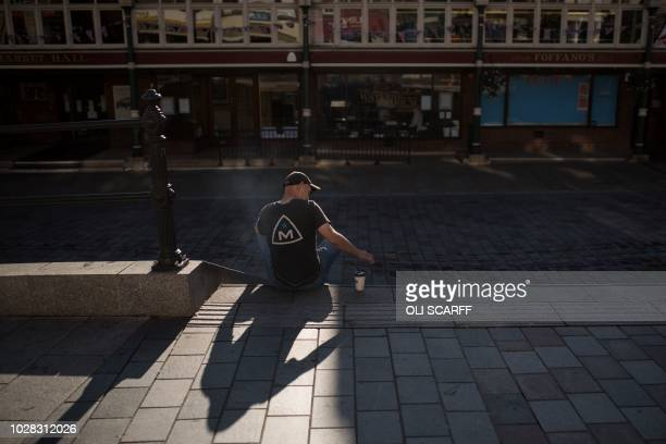 A man sits with a hot drink on High Row a pedestrianised shopping street opposite the covered market in the town centre of Darlington northern...