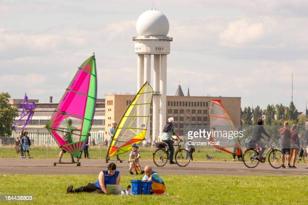 A man sits with a laptop on the ground as enthusiasts exercis wind skating on a longboard with a mounted sail across a runway at former Tempelhof...