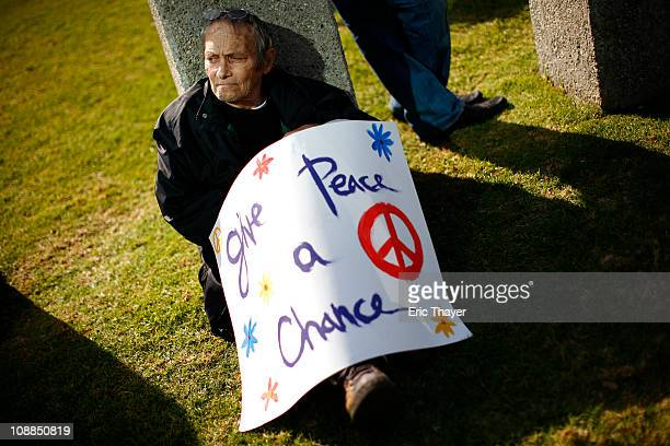 A man sits with a sign at a protest against the regime of Egyptian President Hosni Mubarak February 5 2011 in the Westwood neighborhood of Los...