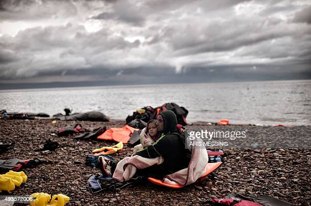 A man sits with a young girl wrapped in a blanket on the shore after arriving with other refugees and migrants on the Greek island of Lesbos after...