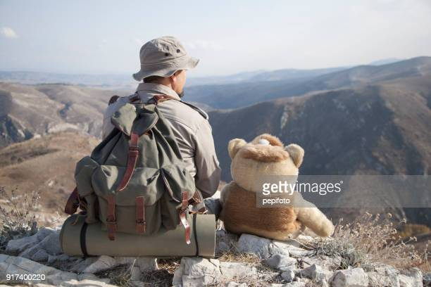 Man sits  with bear toy
