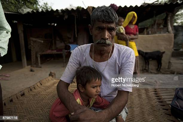 A man sits with his daughter in a slum area near a newly dug roadway April 21 2009 where agricultural areas he and members of twelve families have...