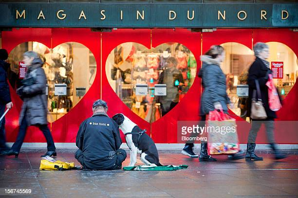 A man sits with his dog and asks for charity outside a Magazin du Nord store in Copenhagen Denmark on Monday Nov 19 2012 Denmark's twoyear yields...