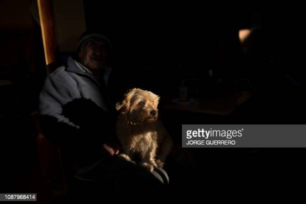 A man sits with his dog in Totalan southern Spain on January 24 2019 Miners were lowered on a cage to rescue twoyearold Julen Rosello who fell down a...
