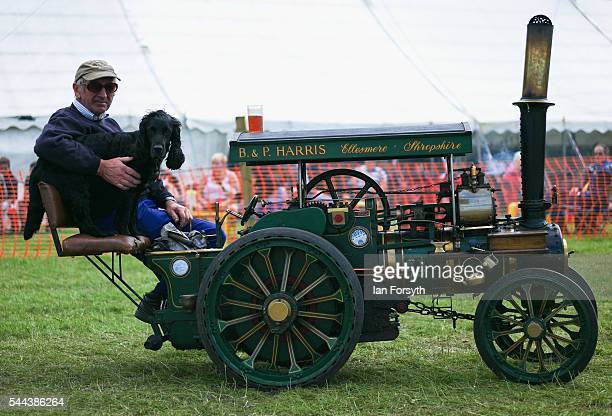 A man sits with his dog on his miniature steam engine at the annual Duncombe Park Steam Fair on July 3 2016 in Helmsley England Held in the...