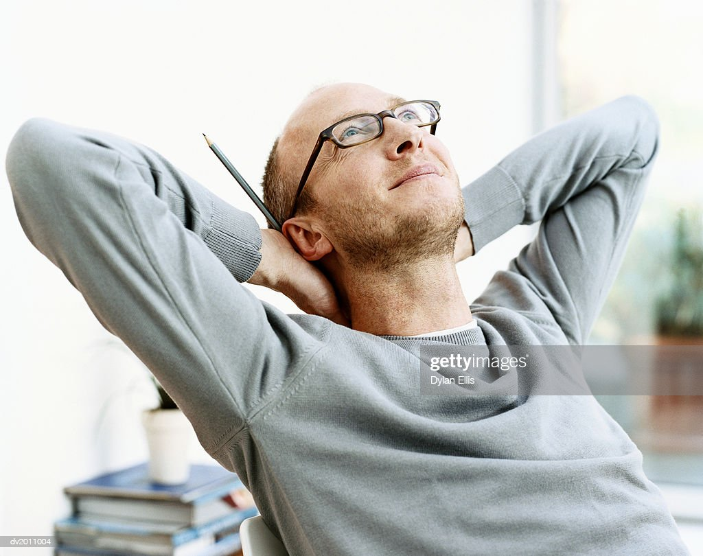 Man Sits With His Hands Behind His Head, Looking Up in Inspiration : Stock Photo