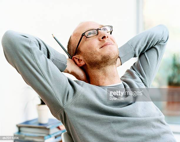 man sits with his hands behind his head, looking up in inspiration - authors ストックフォトと画像