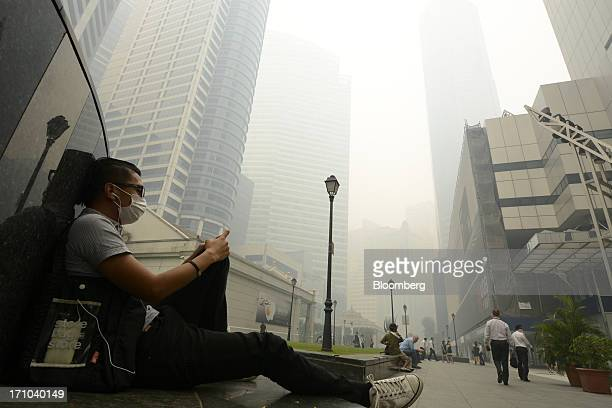 Man sits with his headphones at Raffles Place in Singapore, on Friday, June 21, 2013. Singapore's smog hit its worst level, blanketing the city-state...