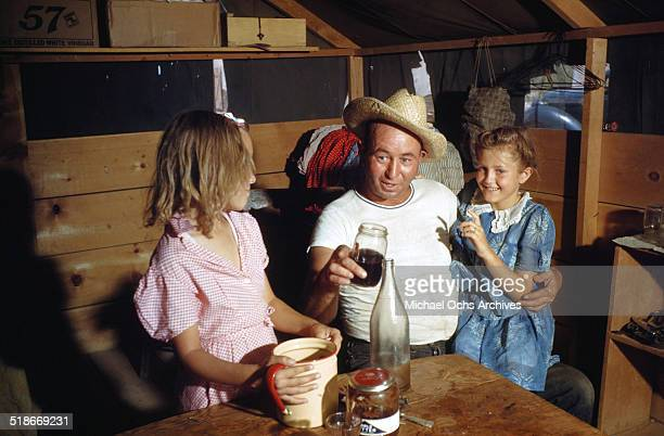 A man sits with his young daughters in their home at Tent City Nevada housing for workers and thier families at the Basic Magnesium Incorporated a...