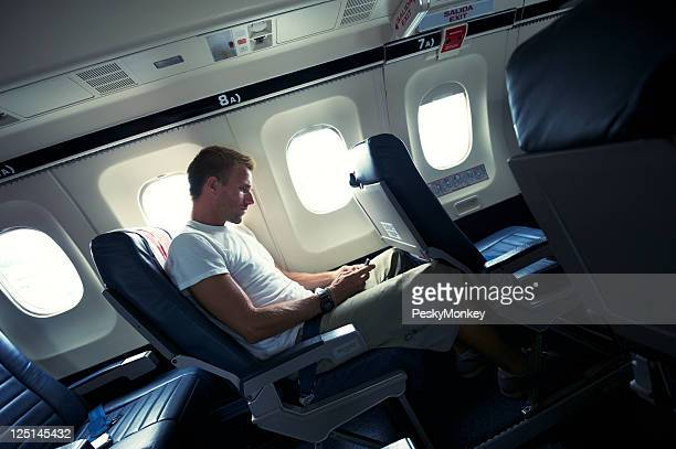 Man Sits with Smartphone in Small Airplane Cabin