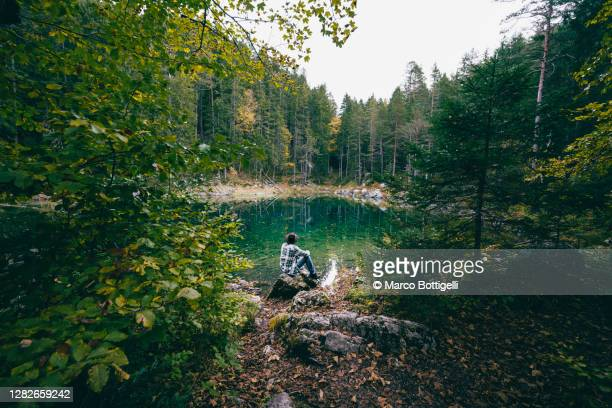 man sitting admiring an emerald lake in the forest - scène tranquille photos et images de collection
