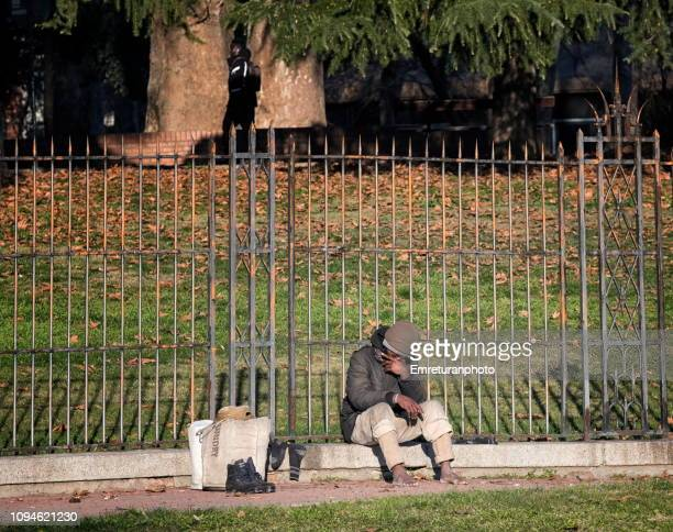 man sitting against a fence on sunny day ,bologna. - emreturanphoto stock pictures, royalty-free photos & images
