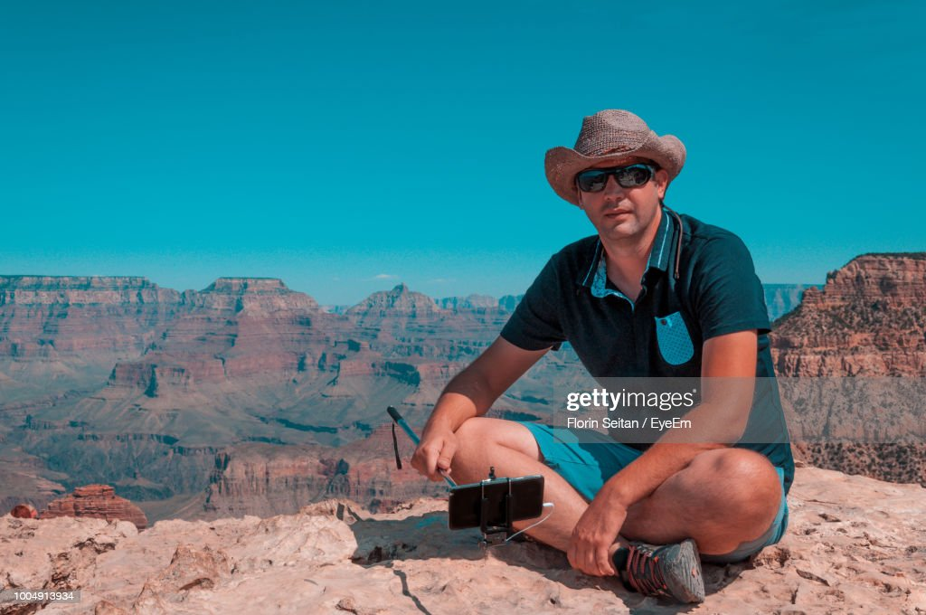 Man Sitting Against Clear Blue Sky At Grand Canyon National Park : Stock Photo