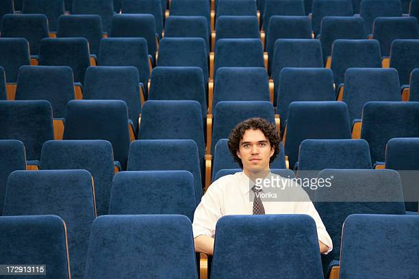 Man sitting alone among empty blue seats in an auditorium