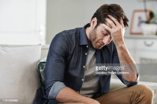 man sitting alone at home looking sad and distraught - one man only stock pictures, royalty-free photos & images