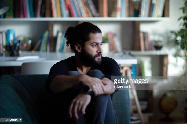 man sitting alone at home looking sad and distraught - suicide stock pictures, royalty-free photos & images