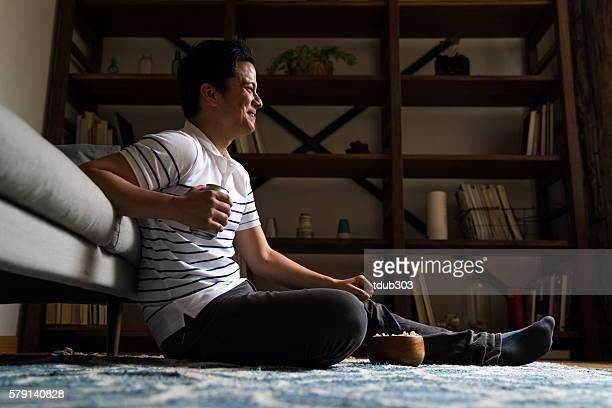Man sitting alone in dark room watching TV