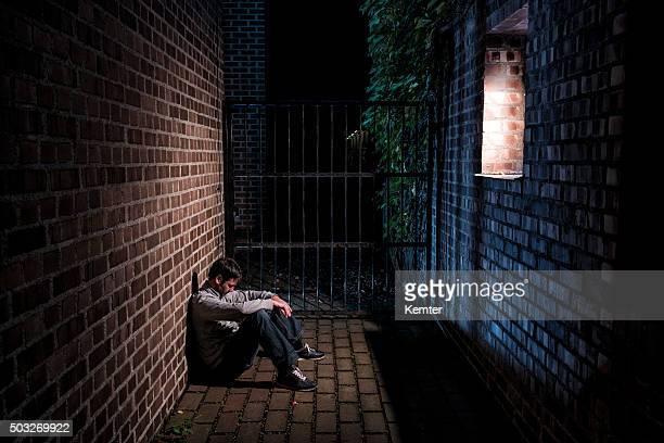 man sitting alone outside at night below window