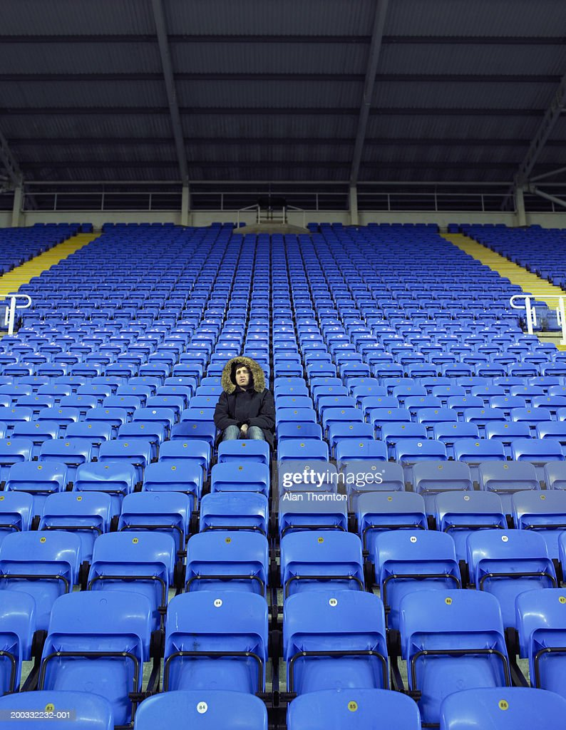 Man sitting amongst rows of blue seats in stadium : Stock Photo