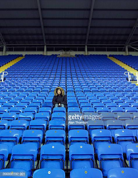 man sitting amongst rows of blue seats in stadium - empty bleachers stockfoto's en -beelden